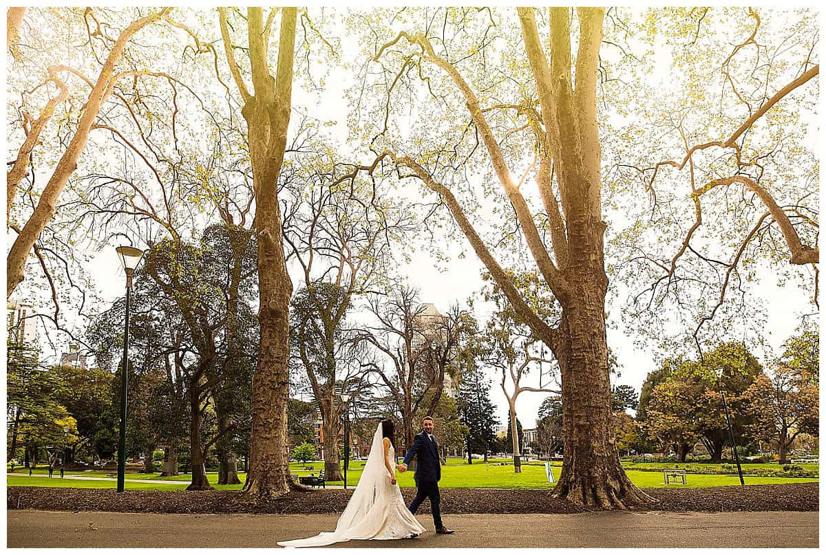 Wedding Couple strolling through Carlton Gardens, Melbourne - Hacking Creative Wedding Photography